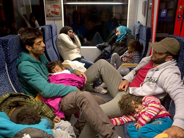 Migrants rest on a train to Vienna as they leave from Nickelsdorf. Thousands of migrants streamed into Austria, desperate to travel on to Germany after days of ugly standoffs with authorities in Budapest's train station. (AFP Photo)