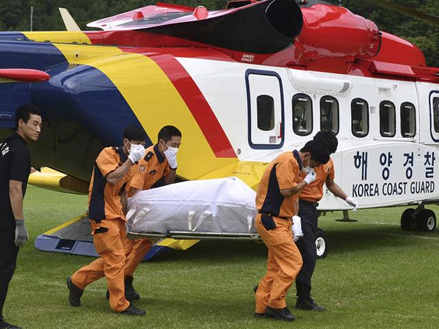 A victim's body who was on board a capsized fishing boat in the water off the resort island of Jeju, is carried by rescue workers upon its arrival in Haenam, South Korea. (Newsis via AP Photo)