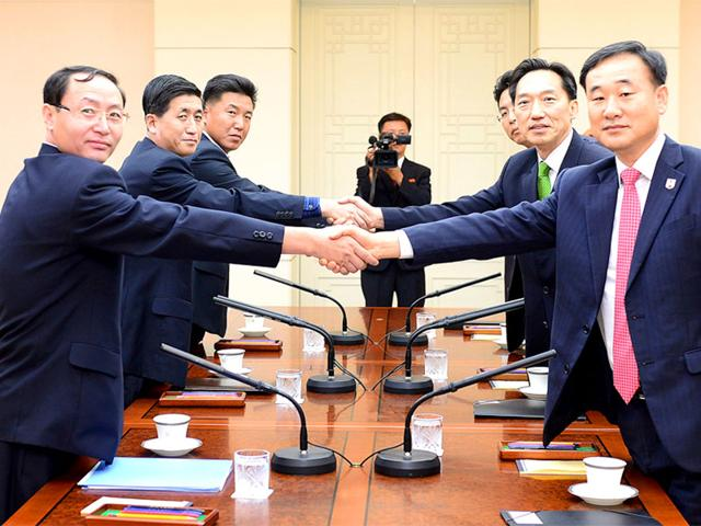 This handout picture released by the South Korean Unification Ministry shows South Korean chief delegate Lee Deok-Haeng (2nd R), executive committee member of South Korean Red Cross, shaking hands with his North Korean counterpart Pak Yong-Il (2nd L) during their meeting at the border truce village of Panmunjom in the Demilitarized Zone dividing the two Koreas. (AFP Photo/The South Korean Unification Ministry)