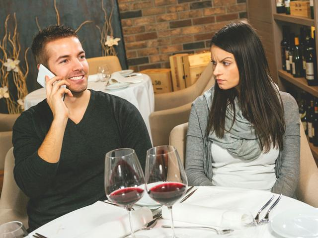 Snubbing your partner by checking your phone during a date or while having a conversation could be ruining relationships and making people depressed. (Shutterstock Image)
