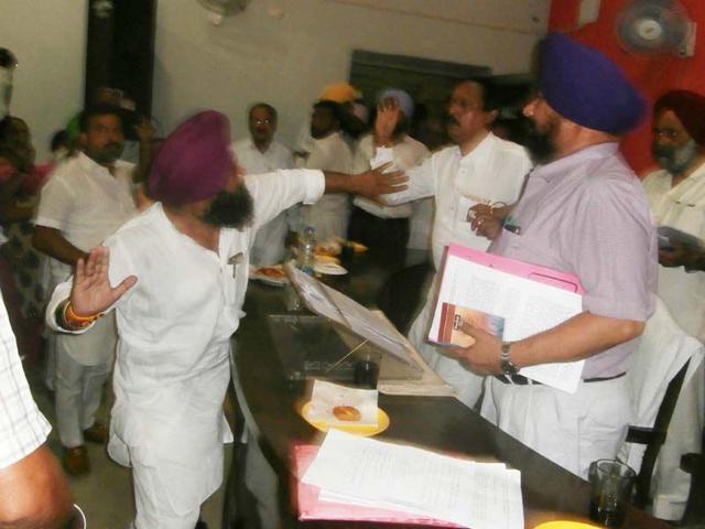 City SAD president Balbir Singh Bittu trying to hit Batala municipal council president from the BJP Naresh Mahajan in the meeting hall of the House on Monday. (HT PHOTO)