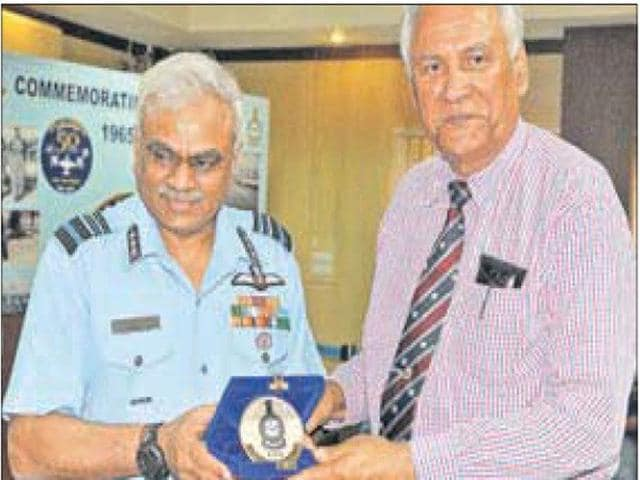 Flight Lieutenant Alfred Tyrone Cooke (retd) (right) handing over his Vir Chakra to an Air Force official in Ambala. (Keshav Singh/HT)