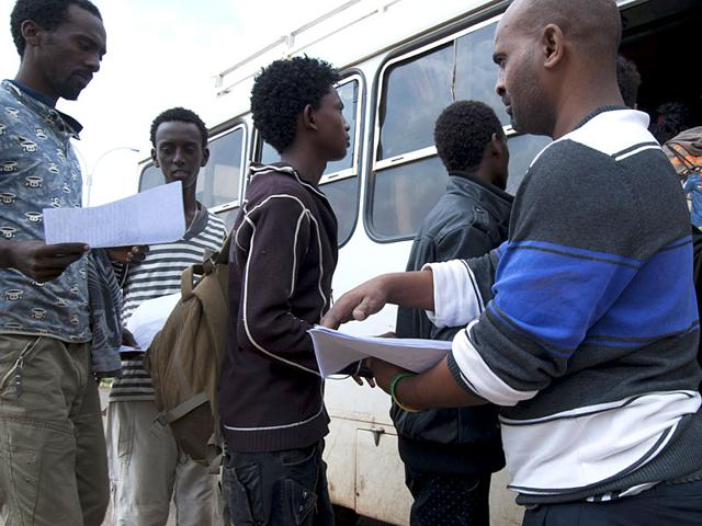 Eritreans refugees get onto a bus after being registered by the Ethiopian authorities at the Hitsats refugee camp in Ethiopia. (AFP Photo)
