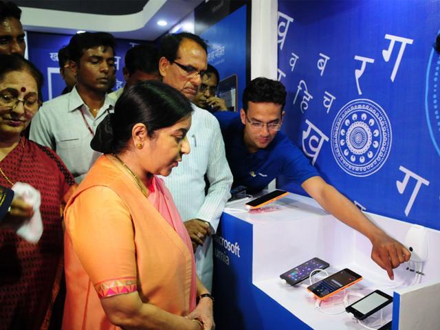 A Microsoft representative demonstrates smartphones with Hindi tools to Sushma Swaraj and Shivraj Singh Chouhan, in Bhopal on Tuesday. (Mujeeb Faruqui/HT)