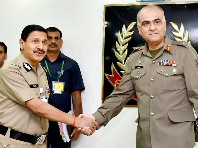 Pakistan Rangers Director General (Punjab) Major General Umar Farooq Burki (R) presents gifts to Indian Border Security Force (BSF) ceremonial guards prior to a meeting at the BSF headquarters in New Delhi on September 10, 2015. Members of the Pakistan Rangers are in India for talks with the Border Security Force (AFP Photo)