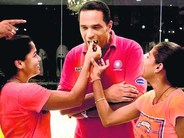 Indian women's hockey team Captain Ritu Rani (R) and Vice-Captain Deepika Thakur (L) with Chief Coach Mathias Ahrens as they celebrate the team's qualification for Rio 2016 Olympics in New Delhi on Saturday. (PTI Photo)