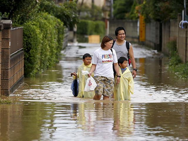 A family wades through a residential area flooded by the Kinugawa river, caused by typhoon Etau, in Joso, Ibaraki prefecture, Japan. (Reuters Photo)