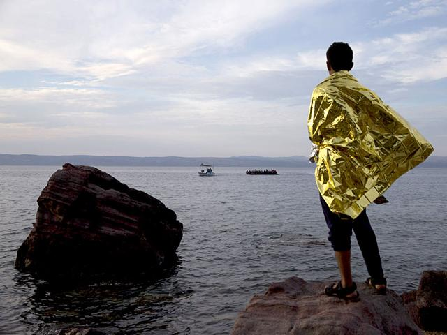 A refugee wrapped in a thermal blanket looks as a dinghy full of migrants and refugees approach the coast of Lesbos island, Greece. (AP Photo)