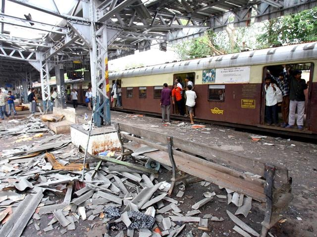 In this file photograph taken on July 12, 2006, commuters walk past the blast site at Mahim railway station in Mumbai, the day after a wave of coordinated blasts on commuter trains in Mumbai. AFP File Photo