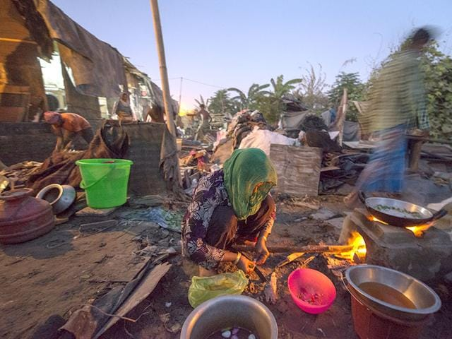 A Rohingya Muslim woman cooks in a semi-dismantled house, after they were forced to give up a section of their refugee camp area by local authorities, at a refugee camp in Kalandi Kunj area of New Delhi, India, on Thursday, September 10, 2015. (Photo by Gurinder Osan/ Hindustan Times)