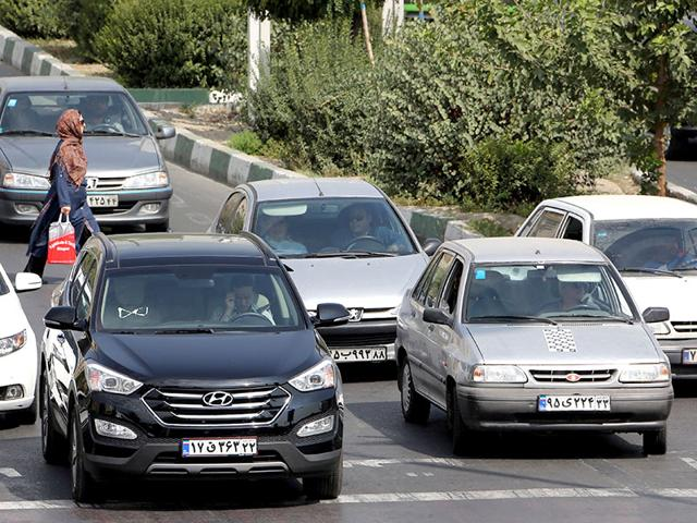 A picture taken on September 12, 2015 shows Iranians driving a Pride car manufactured by SAIPA group (R) and a Hyundai ix45 luxury car (L) in northern Tehran. (AFP Photo/Atta Kenare)