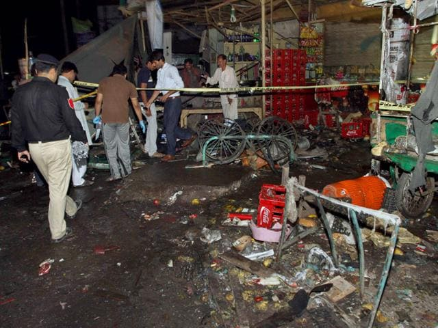 Pakistani police and security officers examine the site of an explosion in Multan, Pakistan on Sunday (AP Photo)