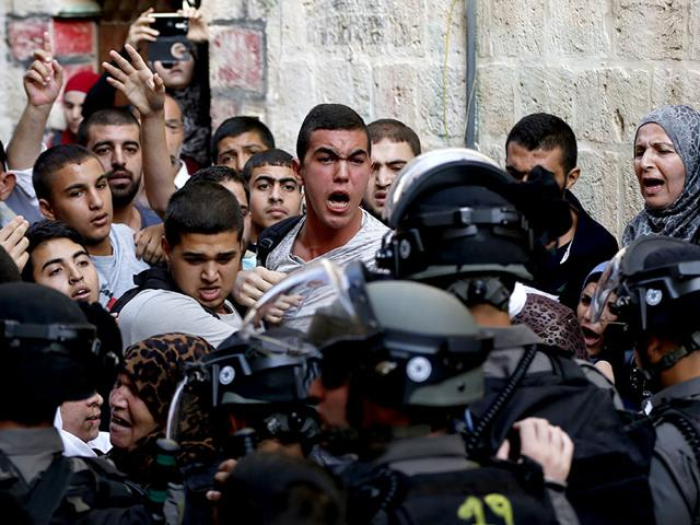 Palestinians shout in front of Israeli security forces who block a road leading to the Al-Aqsa mosque compound in Jerusalem's Old City. Palestinians clashed with Israeli police. (AFP Photo)