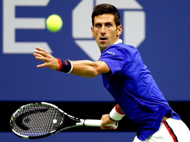 Novak Djokovic, of Serbia, holds up the championship trophy after beating Roger Federer, of Switzerland, in the men's championship match of the US Open tennis tournament. (AP Photo)