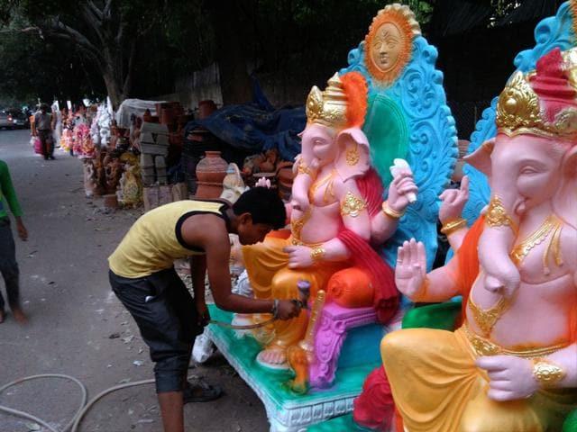 An artisan painting Ganesh idols in South Delhi's Sarojini Nagar market. The market has hardly any seller of clay idols, and is full of PoP ones. (HT Photo/Gulshankumar Wankar)