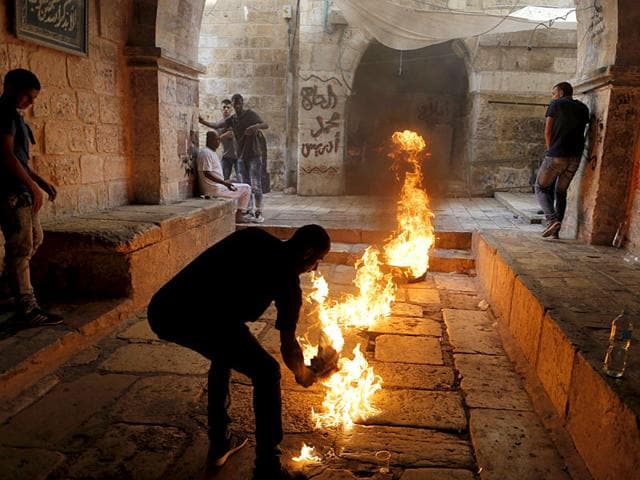A Palestinian protester kicks a burning tyre during clashes between Palestinians and Israeli police officers in Jerusalem's Old City. (Reuters Photo)