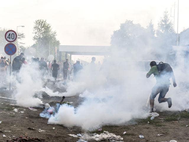 Migrants run away from tear gas thrown by Hungarian anti-riot police officers at the Hungarian border with Serbia near the town of Horgos. (AFP Photo)