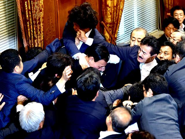 Japanese ruling and opposition lawmakers scuffle at the upper house's ad hoc committee session for the controversial security bills at the National Diet in Tokyo. (AFP Photo)