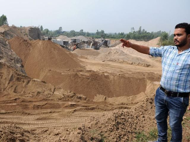 Jaswinder Singh pointing to his land that is under the cave-in threat and is surrounded by pits and a crushersite at Kanju Peer village in Hoshiarpur district on Wednesday. Gurminder Singh/HT