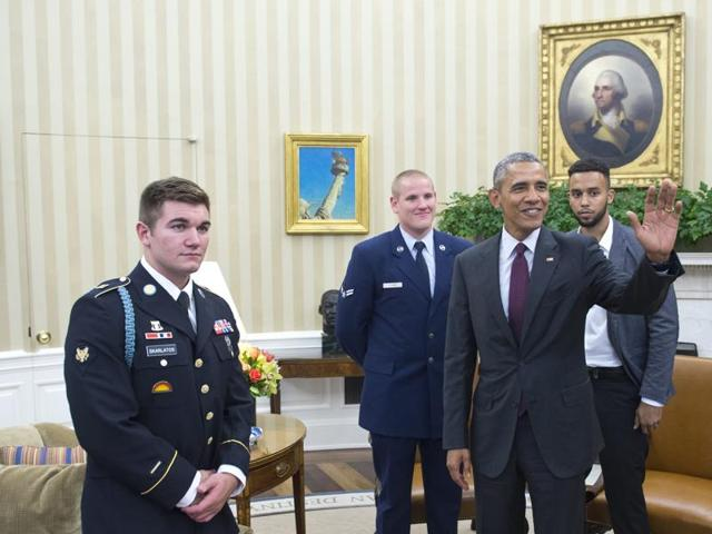 US President Barack Obama waves at a reporter watched by US Army Specialist Alek Skarlatos (L), US Air Force Airman 1st Class Spencer Stone (2nd L), and Anthony Sadler (R) following a meeting on September 17, 2015 in the Oval Office of the White House in Washington, DC.
