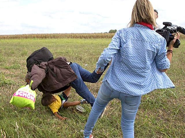 A migrant carrying a child falls after tripping on a TV camerawoman while trying to escape from a collection point in Roszke village, Hungary.