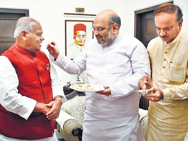 Jitan Manjhi and BJP chief Amit Shah exchange sweets at the end of a seat-sharing pact meeting in New Delhi.