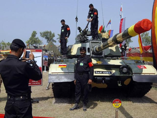 A soldier takes a photograph of his colleague in front of a tank, on display  in Peshawar. The country is in talks with Russia to buy an advanced fighter jet.
