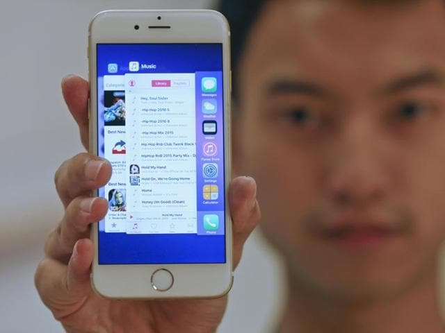 A sales assistant shows features of iOS 9 on an Apple iPhone 6 at an Apple reseller shop in Bangkok.