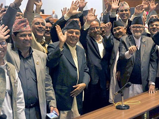 Nepal Prime Minister Sushil Koirala (3R),Unified Marxist Leninist chairman K P Oli (4R), Nepalese Unified Communist Party of Nepal (Maoist) chairman Pushpa Kamal Dahal, known better as Prachanda (4L) and other lawmakers wave while Nepal's parliament passes a new national constitution in Kathmandu.