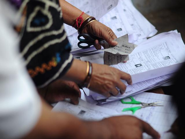 Voters wanting to cast their ballot look at voters lists to find their voting station at a polling station in Mathura, Uttar Pradesh.