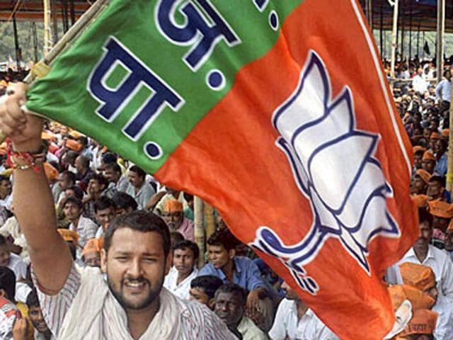 A BJP supporter waves the party flag at NDA's Parivartan Rally in Bhagalpur.