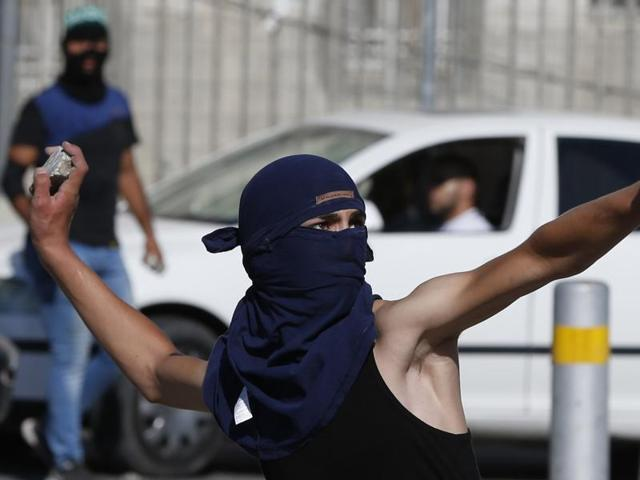 A masked Palestinian youth throws stones towards Israeli security forces during clashes in the Palestinian refugee camp of Shuafat in east Jerusalem.