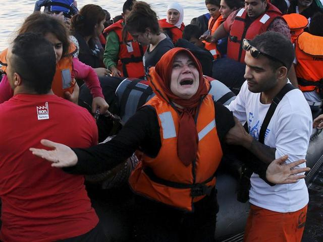 Syrian refugee woman reacts as she and family members jump off a overcrowded dinghy after landing safely on the Greek island of Lesbos after crossing a part of the Aegean Sea from the Turkish coast.