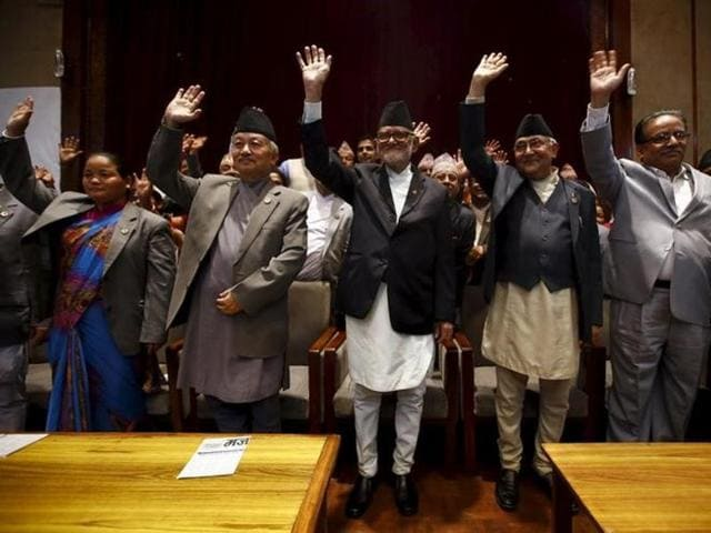 Nepal's Prime Minister Sushil Koirala (C), along with chairman of the Unified Communist Party of Nepal (Maoist) Pushpa Kamal Dahal, also known as Prachanda (R), chairman of the Communist Party of Nepal (Unified Marxist-Leninist) (CPN-UML) Khadga Prashad Oli, also known as KP Oli (2nd R), and Nepalese Constituent Assembly chairperson Subash Chandra Nemwang (2nd L), waves toward media personnel after signing the copy of constitution at the parliament in Kathmandu.