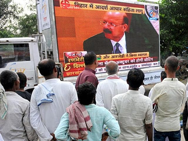 Bihar gets into election mood: People flock before a giant TV screen set up on the roadside in Patna, to hear the Bihar poll announcement by Election Commission .
