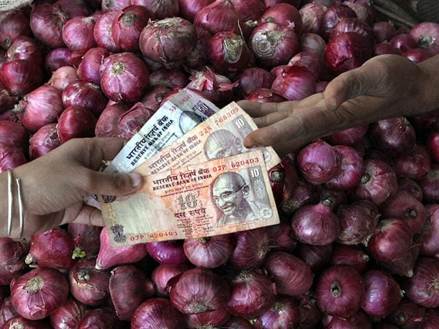 A vendor receives money from a customer as he sells onions near Paharganj in New Delhi .