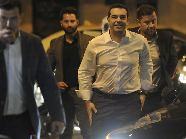Leader of the left-wing Syriza party and former Prime Minister Alexis Tsipras, center, surrounded by his security arrives at the headquarters of his party in Athens, Sunday, Sept. 20, 2015. Tsipras appeared poised for victory in Greece's early election Sunday, but falling short of an absolute majority needed to form a government.