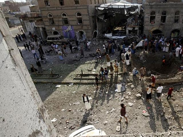 People gather at the site of Saudi-led air strikes in Yemen's capital Sanaa September 19, 2015.