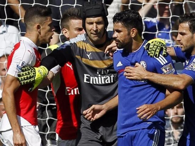 Arsenal's Brazilian defender Gabriel Paulista, left, and Chelsea's Brazilian-born Spanish striker Diego Costa, second from right, are separated by Arsenal's Czech goalkeeper Petr Cech, centre, in a clash during the English Premier League match at Stamford Bridge, London, on September 19, 2015.