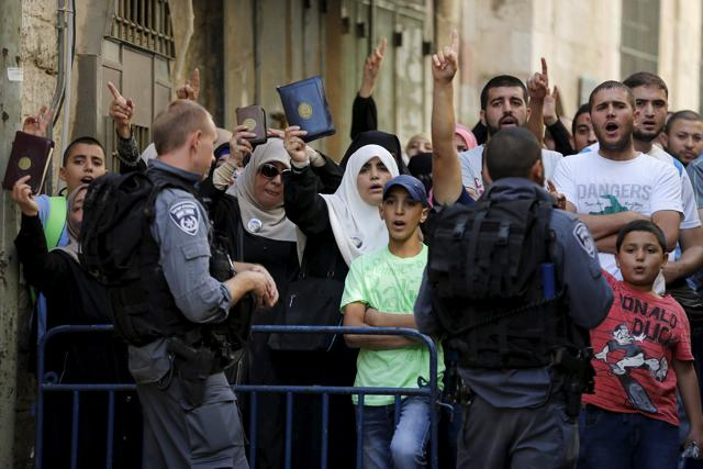 Israeli policemen prevent Palestinian women from entering the compound which houses al-Aqsa mosque, known by Muslims as the Noble Sanctuary and by Jews as the Temple Mount, in Jerusalem's Old City.