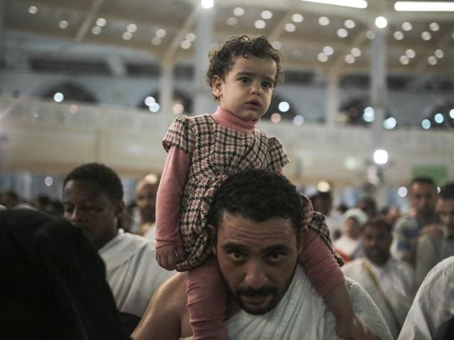 A Muslim pilgrim carries his daughter as they circle the Kaaba, the cubic building at the Grand Mosque in the Muslim holy city of Mecca, while performing Tawwaf, an anti-clockwise movement around the Kaaba and one of the main rites of the annual Pilgrimage, known as hajj, in Saudi Arabia.