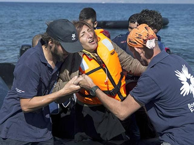 Volunteers help an Afghan woman after she arrived aboard a dinghy from Turkey, to the island of Lesbos, Greece. A girl, about five-years-old died and at least 13 undocumented refugees and migrants were missing after a boat overturned off Lesbos island.