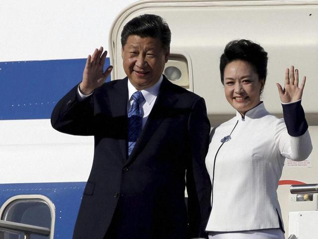 Chinese President Xi Jinping, left, and his wife Peng Liyuan wave upon arriving in Seattle.