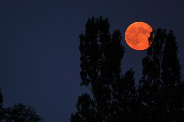 A supermoon is seen on September 9, 2014 from the French city of Luynes. A supermoon happens when a full moon coincides with the its closest approach to the Earth.