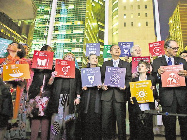 Secretary-general Ban Ki-moon (centre) and others hold banners depicting the 17 SDGs outside the United Nations headquarters, New York, on Tuesday.(Getty Images)