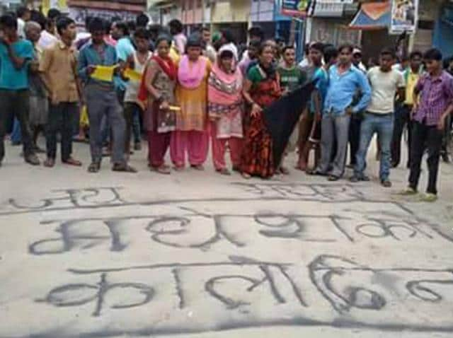 Madheshi people stand near a street of Banke district as they protest against the new constitution of Nepal .