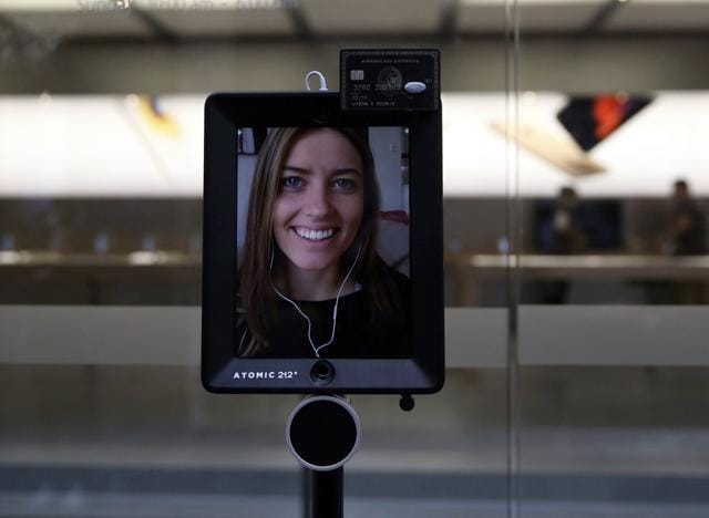 Lucy Kelly is seen on a screen attached to a 'telepresence robot', which she used to purchase her iPhone 6s during the official launch at the Apple store in Sydney, Australia.