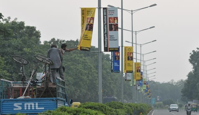 Municipal Corporation officials removing illegal hoardings put up by the UT administration on the central verge of the road dividing Sector 16 and 17 in Chandigarh on Thursday.