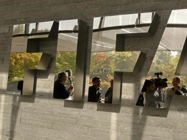 Journalists are reflected in a logo at the FIFA headquarters after a meeting of the executive committee in Zurich October 4, 2013.