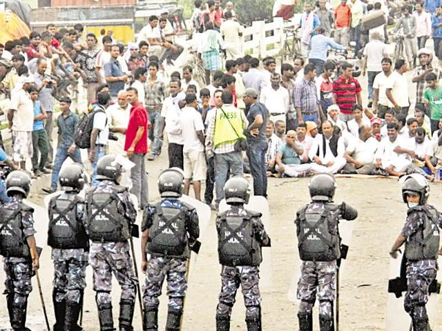 Nepalese policemen face protestors belonging to ethnic and religious groups dissatisfied with Nepal's new constitution adopted on Sunday, in Birgunj, a town bordering India in Nepal.